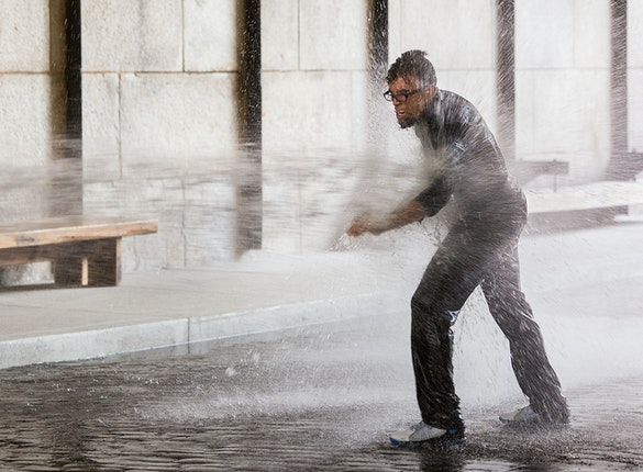 The artist walking against a the water from a firehose