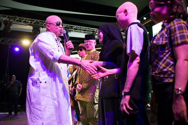 Salif Keita shaking hands with a concertgoer