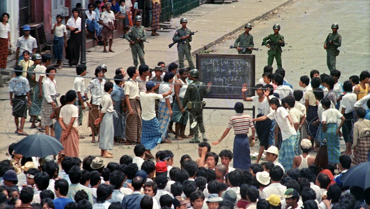 People and soldiers in a street around a chalkboard