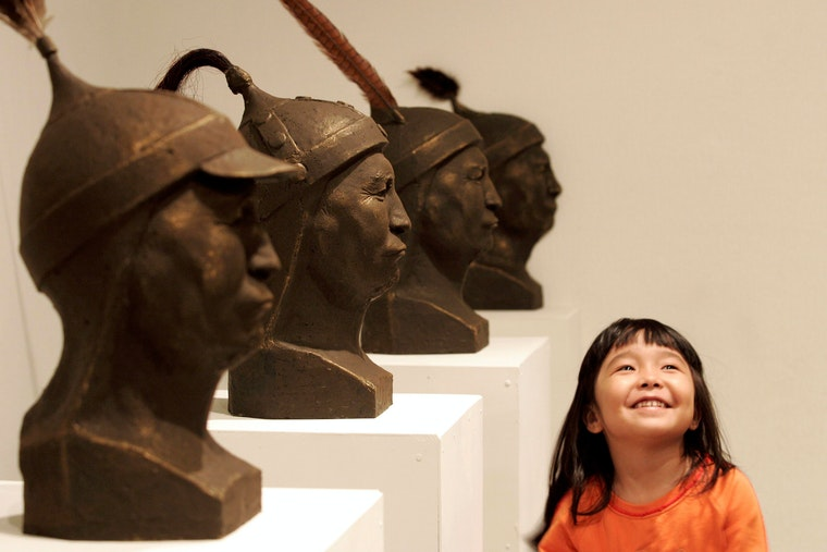 A young girl in a museum stands next to a row of sculpted heads.