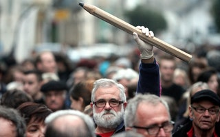 A man holding a giant pencil in the air in the middle of a crowd