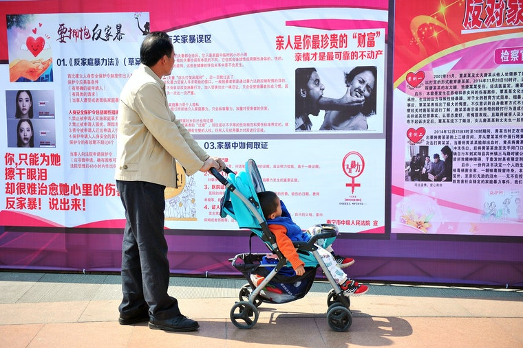 A man with a child in a stroller reading posters