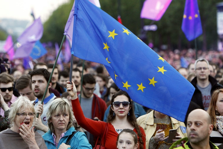 A woman in a crowd holds the EU flag above her head.