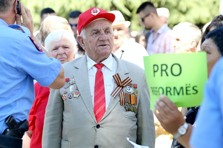 An elderly man with military insignia on his jacket stands amidst a crowd during a sunny day.