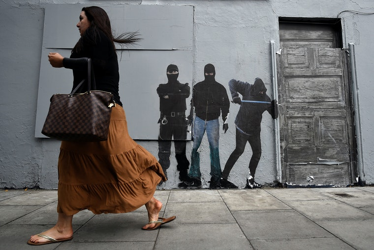A woman walks past a wall with street art painted on it.