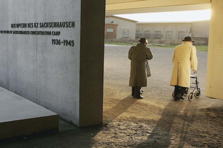 Two people walk into the entrance of a former concentration camp