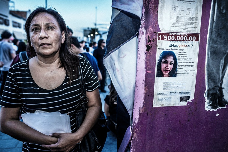 A woman stands next to a missing-person poster in Cuidad Juarez, Mexico.