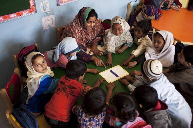 Children gather around a table while listening to their teacher.
