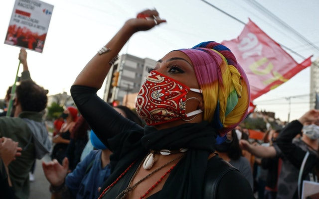 A woman wearing a mask with a raised arm at a protest