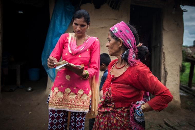 Two women speaking outside a house