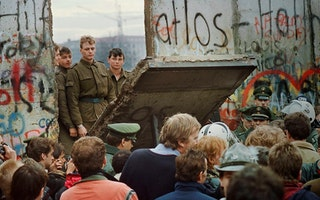 Soldiers standing behind a fallen section of the Berlin Wall