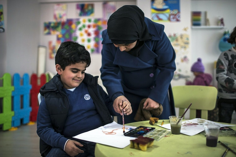 A child and a woman in a classroom using a paintbrush.