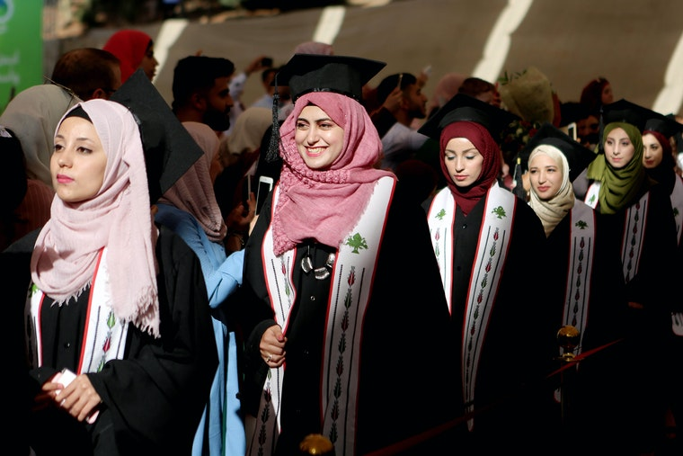 A line of women in graduation caps and gowns.