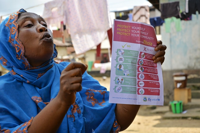 A women teaching Ebola protection