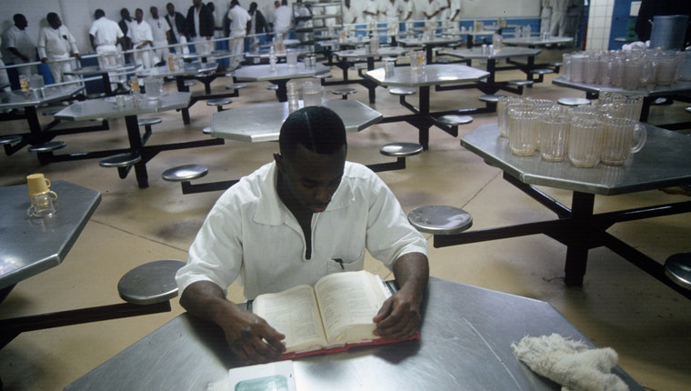 An inmate reading a book at a table