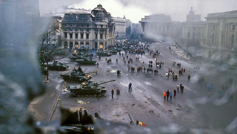 People walking around military tanks below damaged buildings