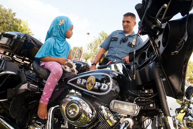 A young girl sitting astride a police motorcycle as the policeman looks on.