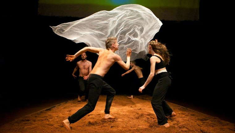 Four performers around a floating sheet