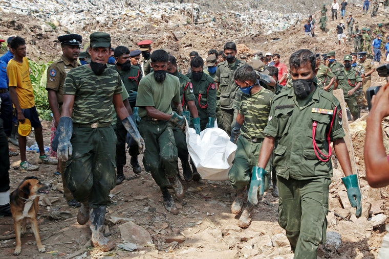 Men in uniforms carry a body away from a mountain of garbage