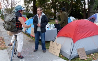 Two people speaking in front of camping tents