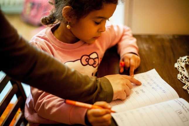 A girl practicing school work in a notebook