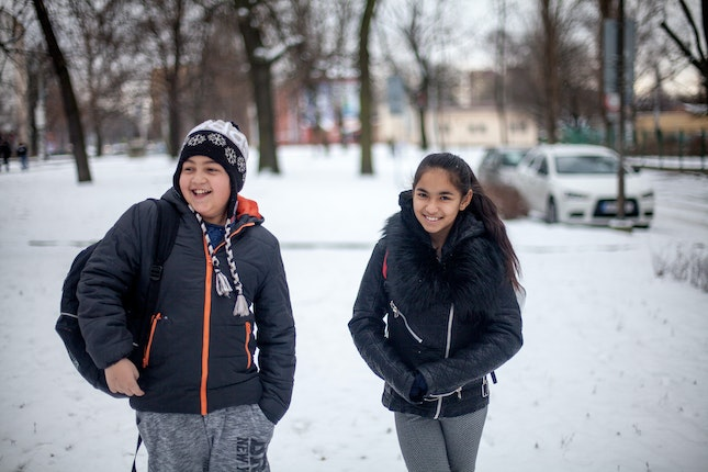 Two friends laughing in the snow on the way to school