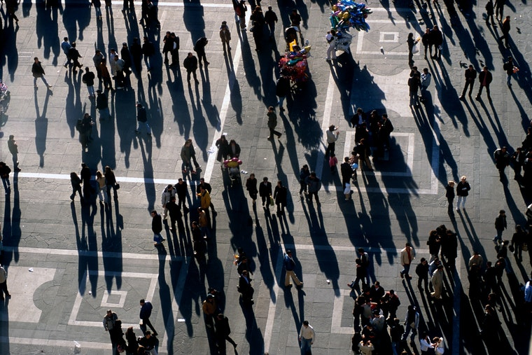 Shadows and people in an open square