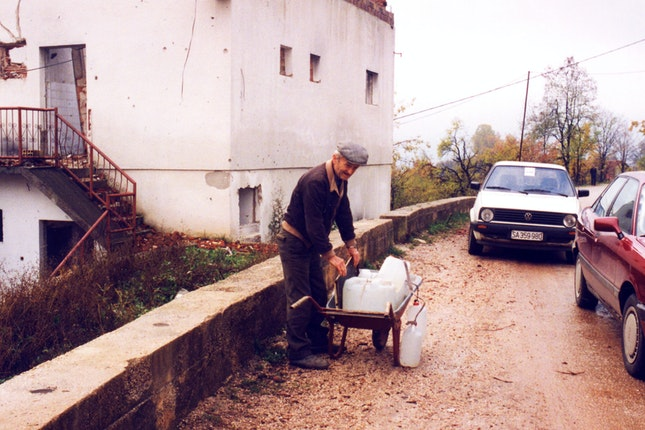 An elderly man stacking bottles of water on a cart
