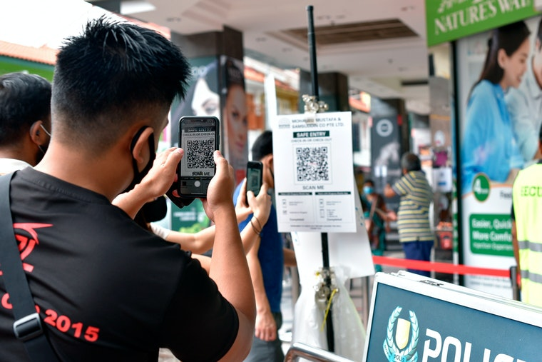 A man scans a QR code at a shopping mall