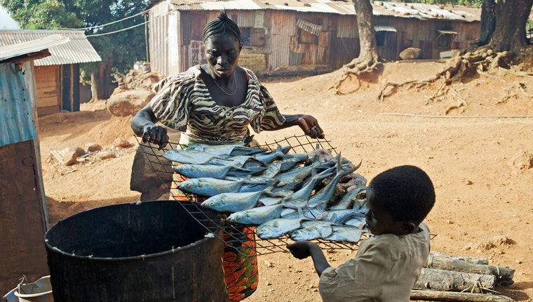 A woman and child carrying a rack of fish