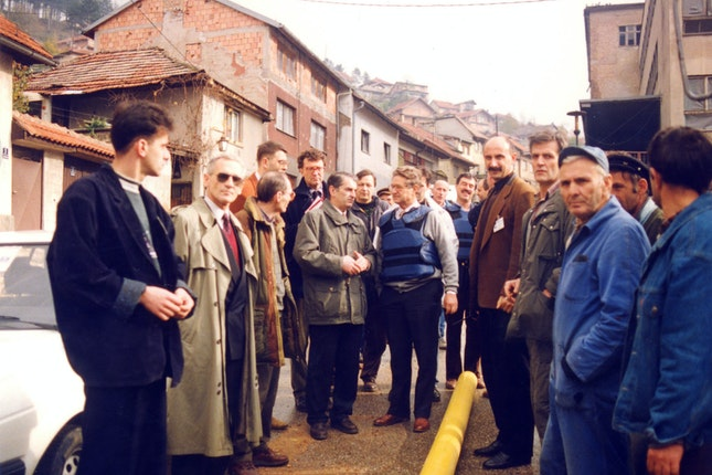 George Soros with a group of people looking at a water main