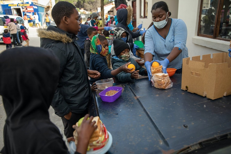 Kids being handed food at a soup kitchen table