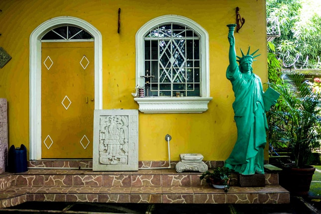 A statue in front of a yellow house