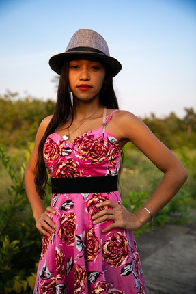 A girl wearing a pink dress and a hat