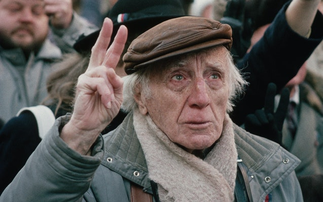 An older man standing in a crowd holding two fingers in the air