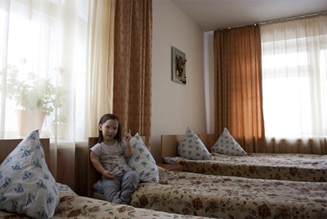 Young girl sitting on bed.