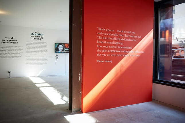 A poem in white letters on a red wall