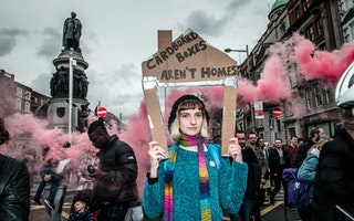A woman holds a cardboard house with pink smoke behind her