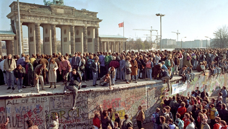 Crowds of people on and around the Berlin Wall