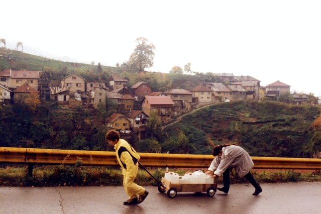 Two young people carting a wagon of water up a steep roadway
