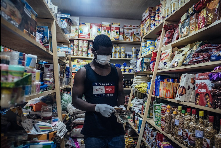 A vendor counts out Nigerian banknotes in a shop