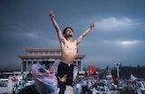 A shirtless man reaching into the air