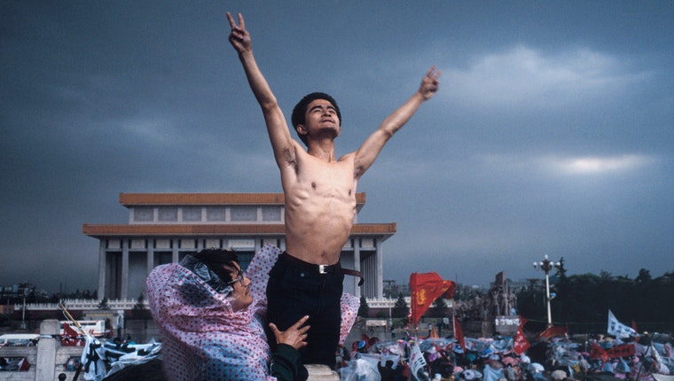 A shirtless man reaching into the air