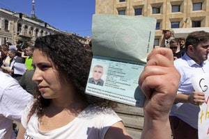 A woman holding up a passport