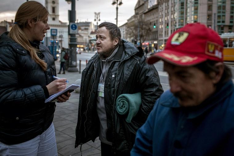 People speaking on a sidewalk on a city street.