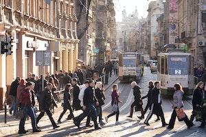 People walking across a street in front of trams
