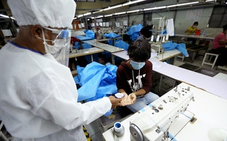 A person in full protective gear sprays the hands of a worker sitting at a sewing machine