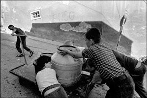 Children push water on cart
