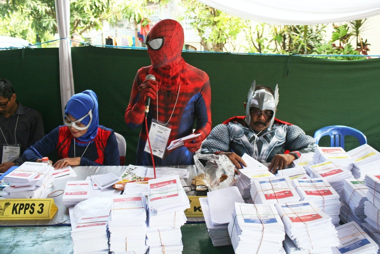 People dressed as superheroes behind stacks of ballots