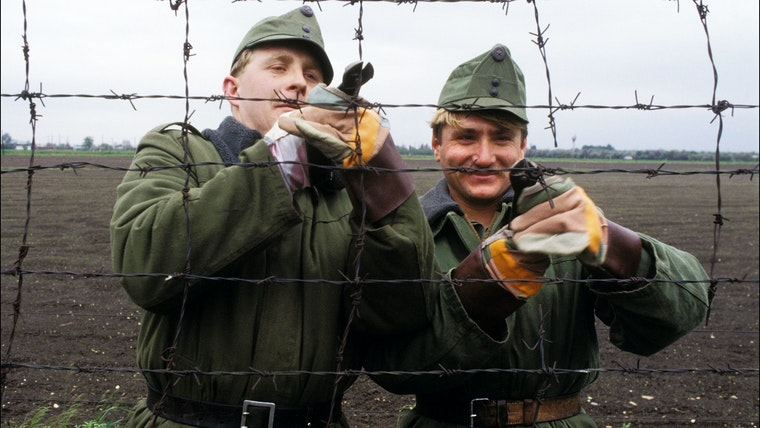 Two men using wire cutters to cut a razor wire fence.